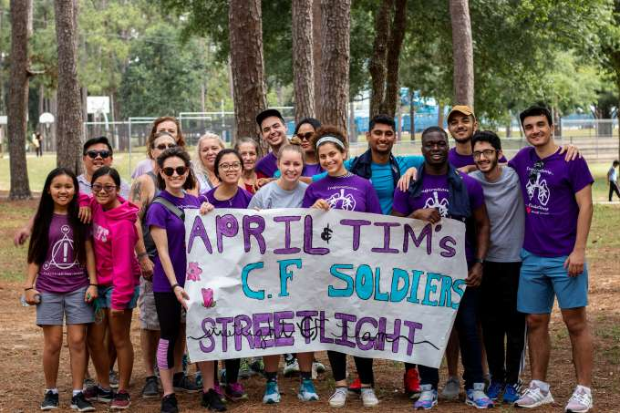 """Streetlight CF Team gathered around a banner that says """"April & Tim's CF Soldiers: Streetlight CF Team"""" outside, surrounded by trees."""