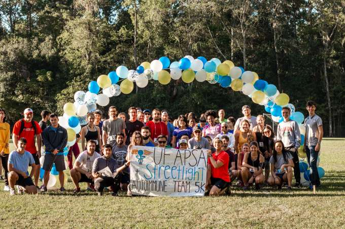 """Streetlight Autoimmune Team and guests of 5k gather around banner that reads """"UF APSA and Streetlight Autoimmune Team."""" Everyone gathered outside with trees in background, standing under a yellow, white, and blue balloon arch."""