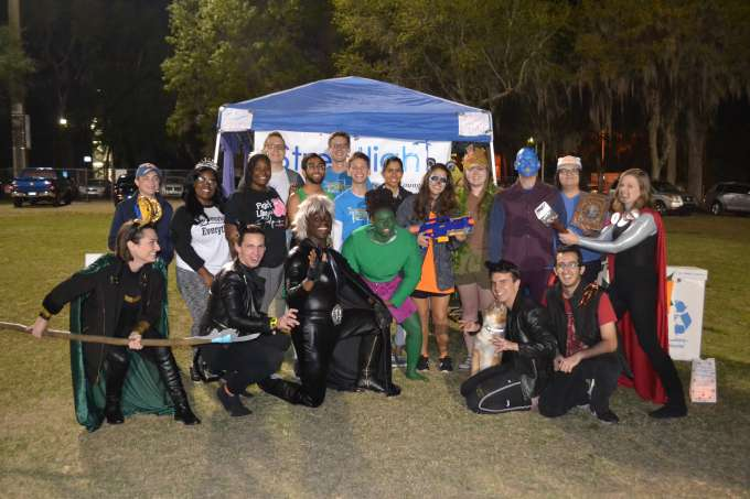 Streetlight Cancer Team gathered around a tent outside, all wearing costumes inspired by superheroes.