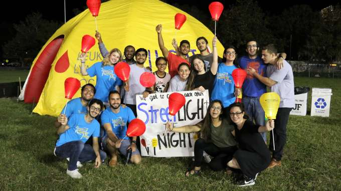 """Streetlight Cancer Team gathered arround banner that reads """"StreetLight the Night."""" Team members are holding red luminaries."""