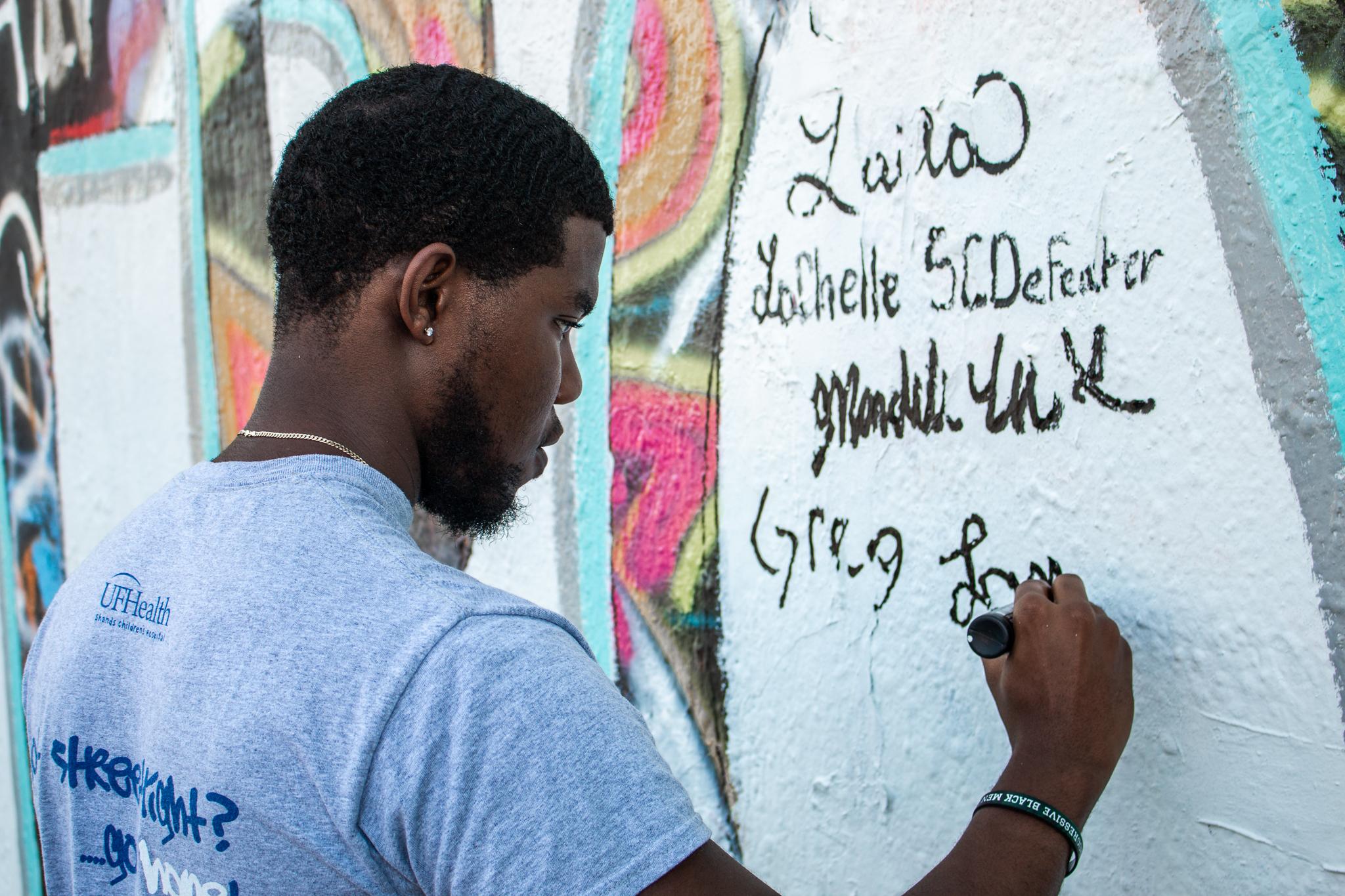Streetlight volunteer signing his name on wall underneath other volunteers' names