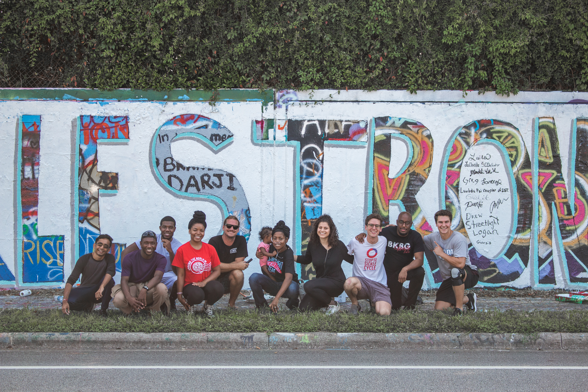"""Streetlight team crouched in front of the 34th Street Wall. Painted on wall is mural that reads """"SickleStrong"""""""
